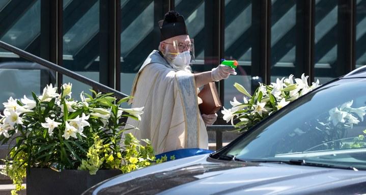 Distanciamiento social: Sacerdote bendice a sus fieles con una pistola de agua